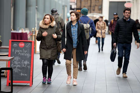 regent: LONDON, ENGLAND - March 12, 2017 Tourists are walking along Oxford Street, intending to do shopping