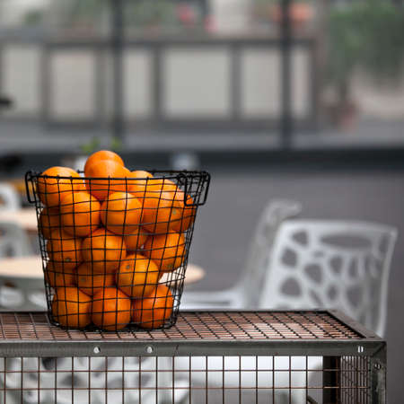 Iron mesh basket with oranges as a table decoration in a street cafe