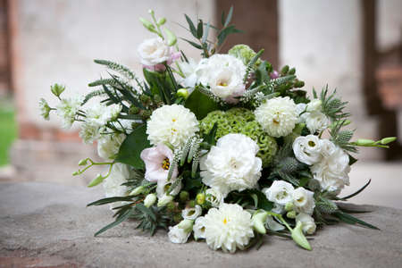 wedding bouquet in white tones of lisianthus, roses, dahlias and eucalyptus lying on stone ancient pavement Stock Photo