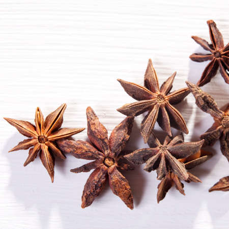 Star shaped anise seeds on white wooden background