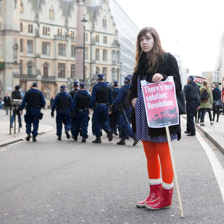marchers: London, UK. 19th Nov, 2016. Students protest against fees and cuts and debt in central London. Girl in red socks with poster One solution -revolution