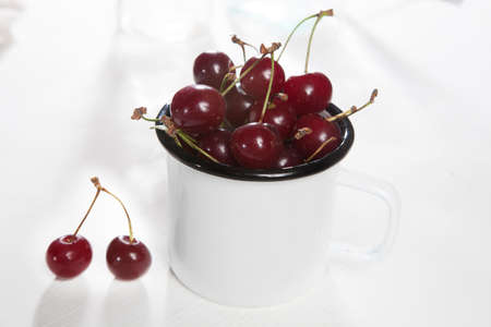 Uzbek ripe cherry in an enameled cup on a white wooden table. Copy space