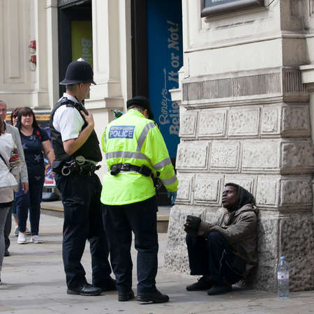 LONDON, ENGLAND - August 11 2017 Police talking to an African American in a gray hoodie who sit to lean to wall Sajtókép