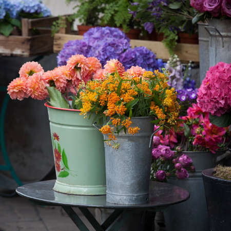 A bouquet of dahlias in a galvanized bucket stands on a chair near the entrance to the store.