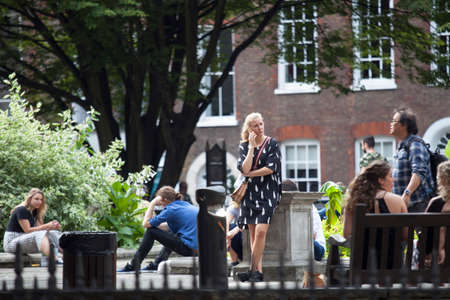 LONDON, ENGLAND - August 20, 2017 Office clerks sit on the grass and have lunch at Golden Square, Soho, exposing faces to the sun