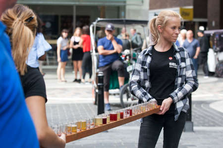 near beer: LONDON, ENGLAND - August 11 2017 Girls promouters keep glasses of beer on a long tray. Girls are advertising a beer restaurant near Covent Garden.