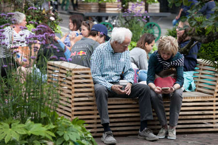 LONDON, ENGLAND - August 11 2017 An elderly couple is sitting on a bench, looking into the phone. A small garden in the center of Covent Garden.
