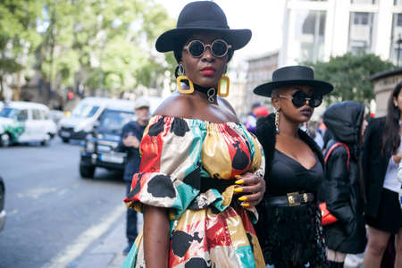 LONDON, ENGLAND - September 15, 2017 Beautiful and stylish woman in colrful yellow nice dress posing during the London Fashion Week. outside Eudon Choi