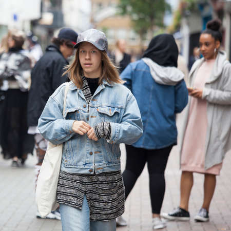 LONDON, ENGLAND - September 11, 2017 A girl in a blue jacket and blue jeans hurries along Oxford Street