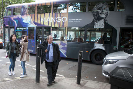 leaned: LONDON, ENGLAND - September 15, 2017 An elderly man in uniform leaned against the pillar. In the background a bus with advertising passes. Editorial