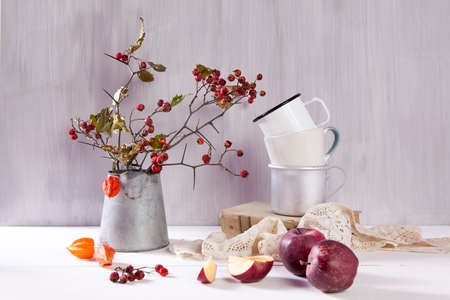 Still-life with a hawthorn, a cup of tea and a kettle on a white wooden background