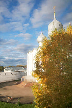 Cathedral against a blue sky with a tree in the foreground in autumn. Kremlin of ancient town of Rostov Veliky.Russia. Golden Ring