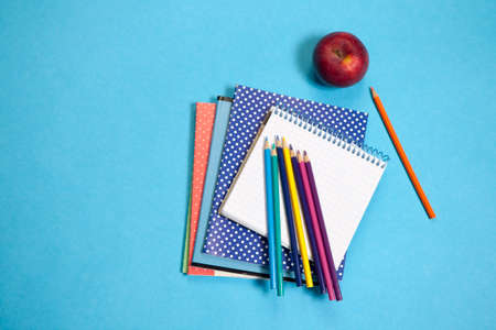 Assorted school supplie with a notebooks on blue background