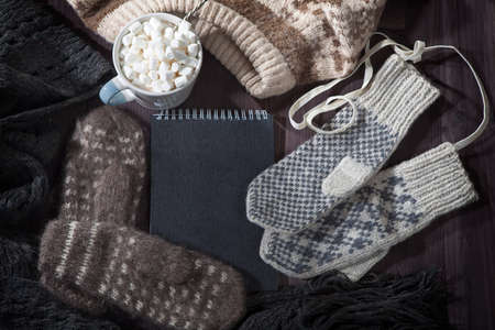 Woolen mittens, scarf and sweater with a black notepad for notes lie on the table. Copy space.