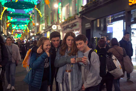 LONDON - DECEMBER 18, 2017: Teenagers make selfies. Christmas lights on Carnaby Street, London UK. Carnaby Christmas lights feature some of the most unusual decorations and lights in London.