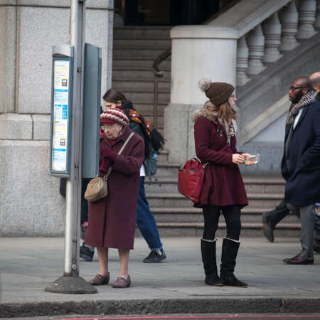 London, UK - December 22, 2017: a girl in a claret coat and a grandmother wearing glasses and a claret coat are standing at a bus stop, waiting for the bus