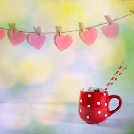 Red cup in a white point is on a white wooden table. Paper hearts hang on the wall Stock Photo