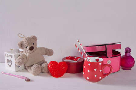 Postcard to Valentine's day with teddy bear, cup in the dots, light and casket on white wooden background