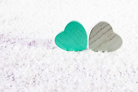 Two wooden green and grey heart on white artificial snow