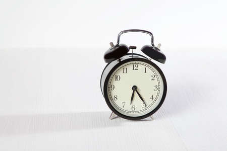 the Clock alarm on white wooden table