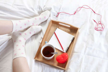 A tray with a cup of coffee, a notepad and a pencil stands on the bed