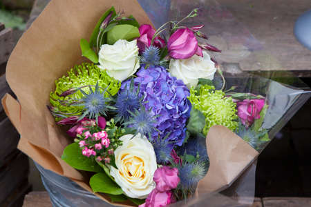 Bouquet of roses, hydrangea and lisianthus in kraft paper in zinc pail for sale