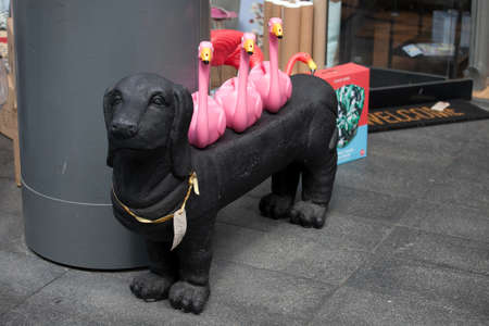 LONDON, UK - August 22, 2017: Black plastic basset dog with pink flamingos on the back at Old Spitalfields Market in London. A market existed here for at least 350 years Editöryel