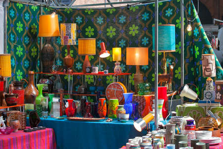 LONDON, UK - August 22, 2017: Multicolored fixtures in the sixties style, chandeliers from the seventies against a background of green in orange flower cloth at Old Spitalfields Market in London.
