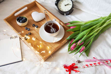A tray with tea and gingerbread in the shape of heart and a bouquet of tulips on the bed Stock Photo