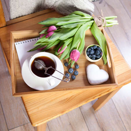A tray with tea and gingerbread in the shape of heart and a bouquet of tulips on the chair