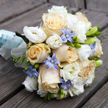 Wedding bouquet of yellow and white  roses and blue fresia  lying on wooden floor Reklamní fotografie