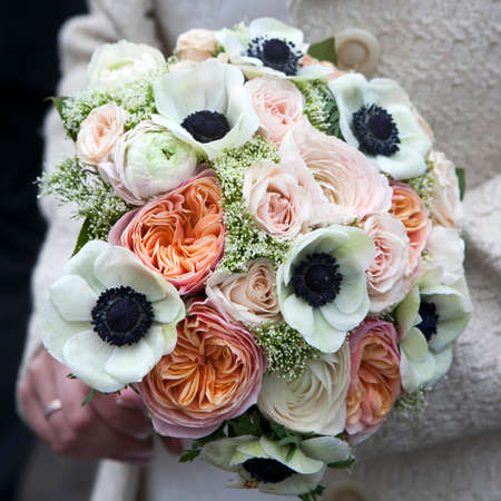 Bride holds wedding bouquet of pink roses and white anemone and pink ranunculus lying on wooden floor