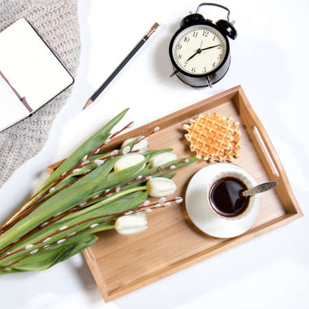 A tray with coffee, white tulips and willow stands on the bed. The alarm clock shows seven in the morning. Stock Photo