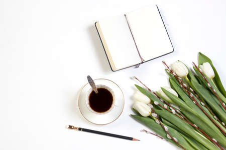 cup of coffee with a notebook and a bouquet of white tulips on a wooden table. Copy space
