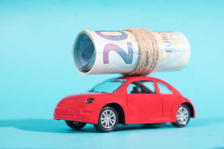 A red toy car carries twenty euros, folded into a tube and tied with twine. Blue background. Copy space Stock Photo