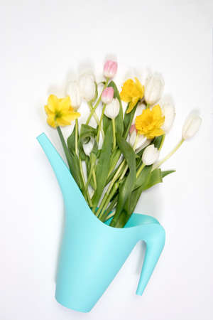 Yellow rubber boots with a bouquet of flowers of yellow daffodils and white and pink tulips. Garden accessories.