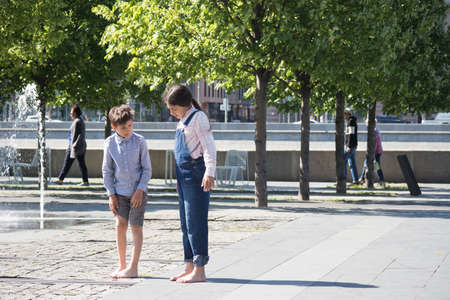 Moscow, RUSSIA - MAY 25, 2018: Boy and girl stand barefoot near fountain Editorial