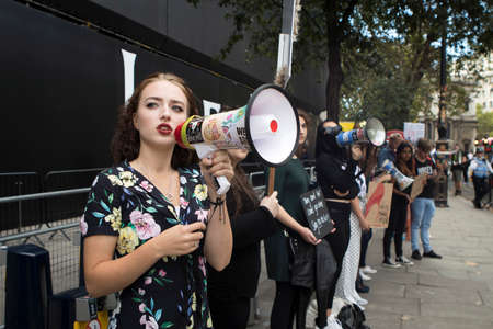 LONDON, UK- SEPTEMBER 14 2018: Beautiful girl in a long fashionable colorful dress with a megaphone protests against the fashion industry 新聞圖片