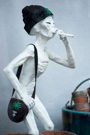 LONDON, ENGLAND - JULY 12, 2018 white sculpture of an alien in a hat smoking a cigarette in the shop window