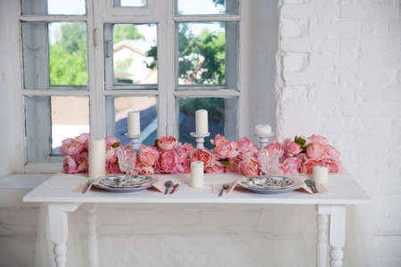 A bouquet of pink orchids, roses and peons decorates the dining table near the window