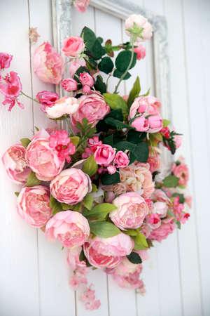 Un bouquet d'orchidées roses, de roses et de péons dans un grand cadre accroché au mur. Banque d'images
