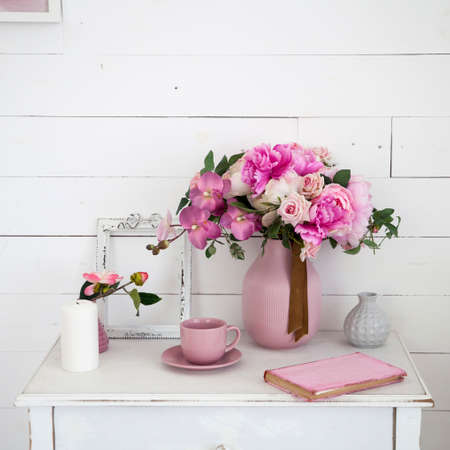 A bouquet of orchids, peonies, roses in a ceramic vase on the bedside table and a stack of books 스톡 콘텐츠
