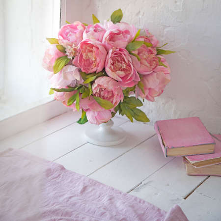 A bouquet of orchids, peonies, roses in a ceramic vase and a stack of books