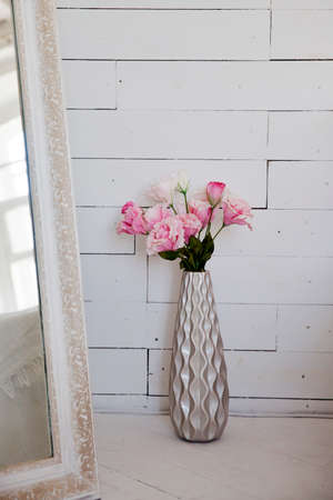 A bouquet of pink carnations near a large floor mirror