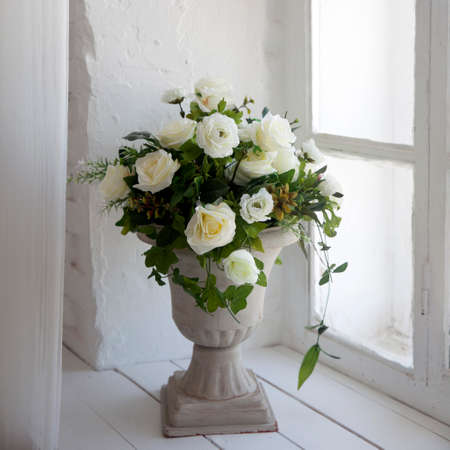 A bouquet of white artificial roses, eucalyptus and ivy in a stone vase on the windowsill near the window