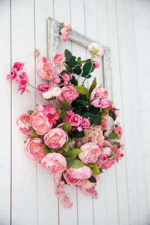 A bouquet of pink orchids, roses and peons in a large frame hanging on the wall.