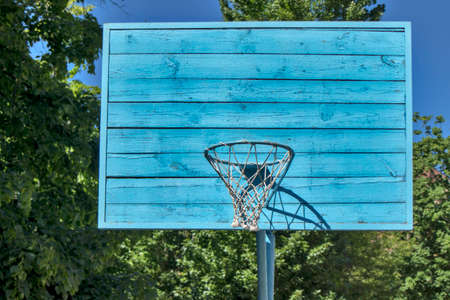 Blue wooden basketball backboard in the park among the linden trees