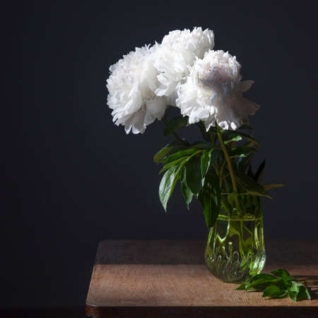 A bouquet of white peonies in a transparent vase on a dark background