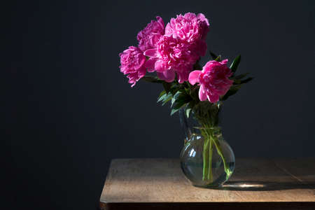 bouquet of a pink peonies in a transparent vase on a dark background