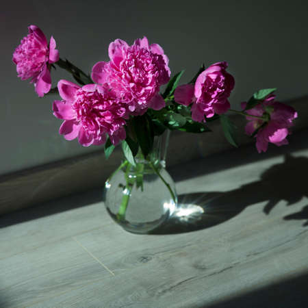 Bouquet of pink peonies is in a glass transparent vase on the floor